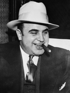 04 May 1932 --- Infamous gangster Al Capone smokes a cigar on the train carrying him to the federal penitentiary in Atlanta where he will start serving an eleven-year sentence. --- Image by © Bettmann/CORBIS